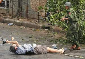 Kenji of APF tries to take photographs as he lies injured after police and military officials fired upon and then charged at protesters in Yangon's city centre
